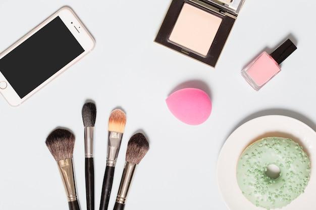 Teléfono inteligente y donut cerca de productos de belleza
