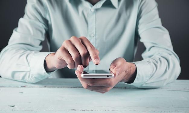 Teléfono inteligente de la mano del hombre en la mesa