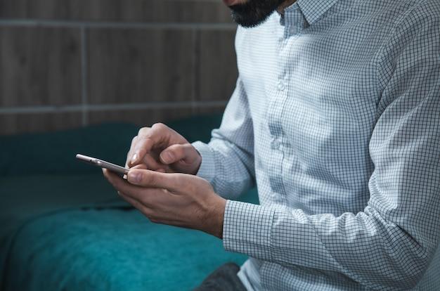 Teléfono inteligente de mano de hombre sentado en la cama
