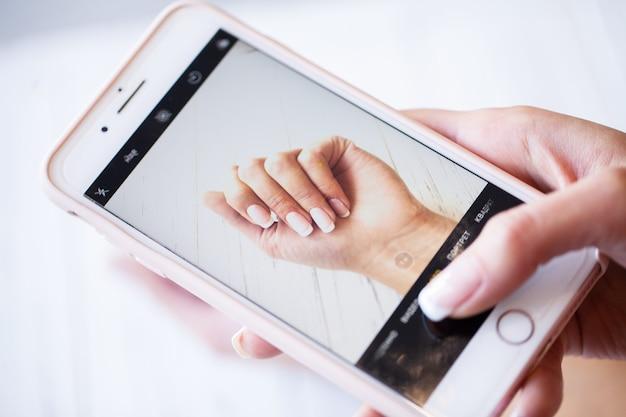 El teléfono inteligente en manos del cliente hace que la foto sea nueva y manicura