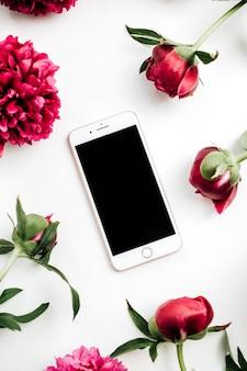 Teléfono inteligente en el marco de flores de peonías rosas sobre fondo blanco. maqueta de vista superior, endecha plana.
