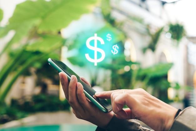 El teléfono inteligente móvil de gadget de uso de mujer gana dinero en línea con el icono de dólar emergente.