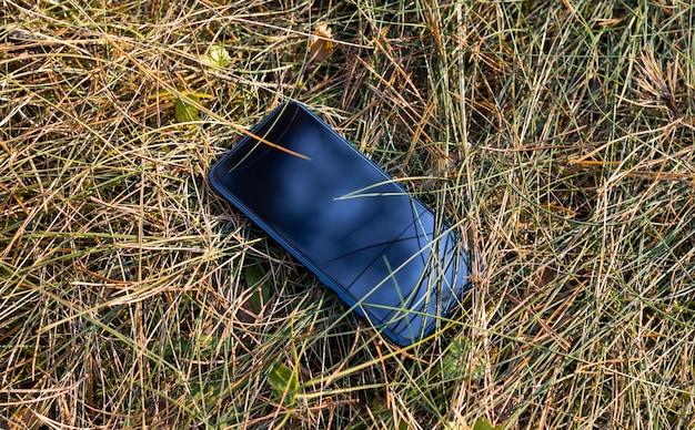 Teléfono inteligente móvil en la hierba - teléfono perdido