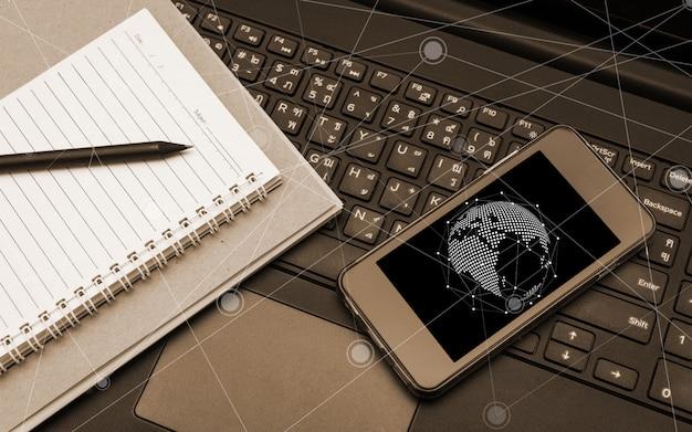 Teléfono inteligente móvil pantalla en negro en el teclado del ordenador portátil