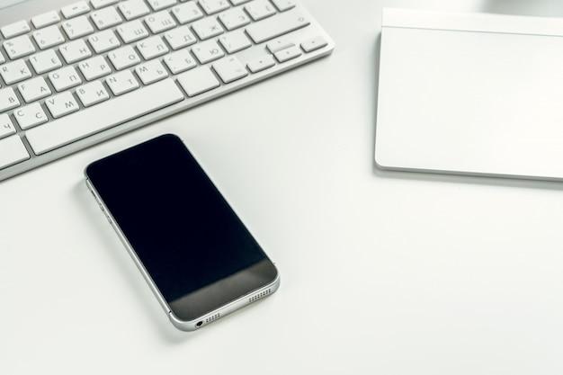 Teléfono inteligente negro cerca de la computadora portátil abierta