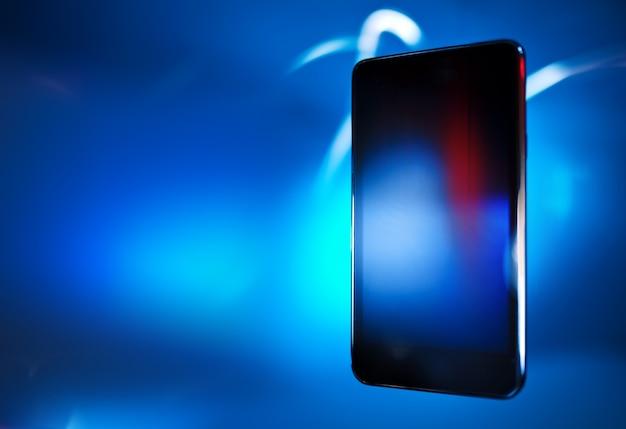 Teléfono inteligente negro sobre superficie de desenfoque azul, concepto, diseño de plantilla
