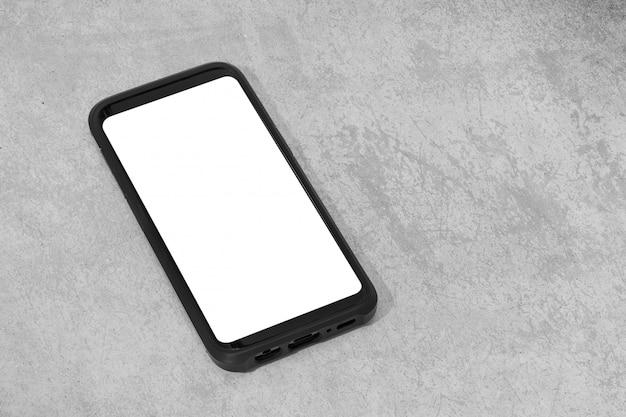 Teléfono inteligente con pantalla blanca aislada sobre fondo de hormigón con textura. simulacros de plantilla. copia espacio