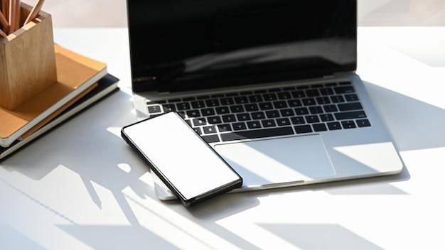 Teléfono inteligente de pantalla blanca está poniendo en la computadora portátil en el escritorio de trabajo.