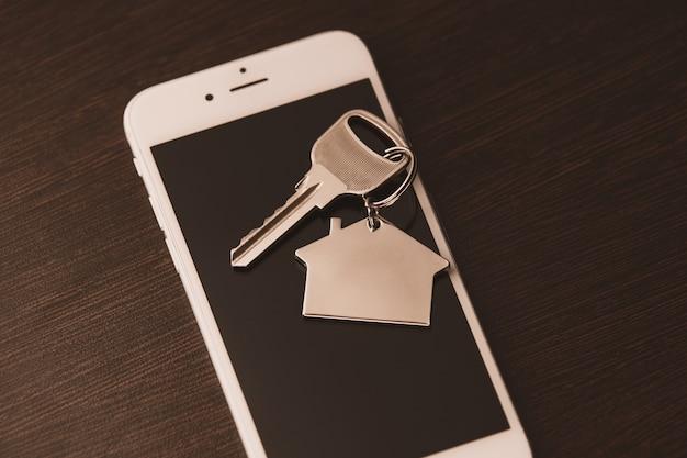 Teléfono inteligente con pantalla en blanco y llave de control de alarma remota para automóvil encendida