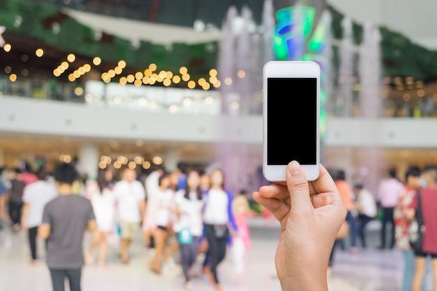 Teléfono inteligente con pantalla en blanco en la mano en borrosa en centro comercial de fondo, el concepto de compras en línea, las compras por teléfono inteligente