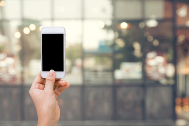Teléfono inteligente con pantalla en blanco en la mano en borrosa en el fondo del centro comercial
