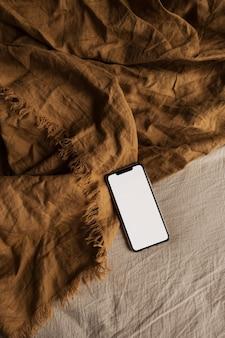 Teléfono inteligente de pantalla en blanco en manta de jengibre.