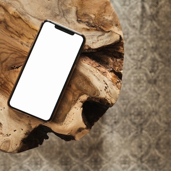Teléfono inteligente de pantalla en blanco con maqueta de espacio de copia vacía en taburete y alfombra de madera maciza
