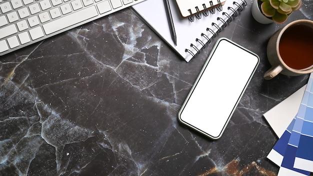 Teléfono inteligente con pantalla en blanco sobre mesa de mármol. espacio de trabajo.