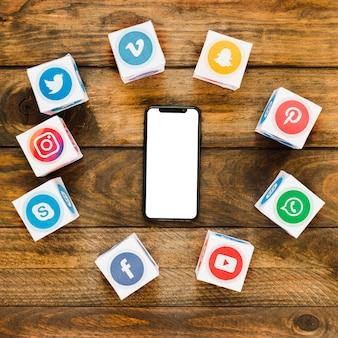 Teléfono inteligente con pantalla táctil rodeado de cajas de iconos de aplicaciones multimedia