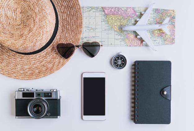 Teléfono inteligente de pantalla vacía con accesorios y artículos de viaje, concepto de viaje