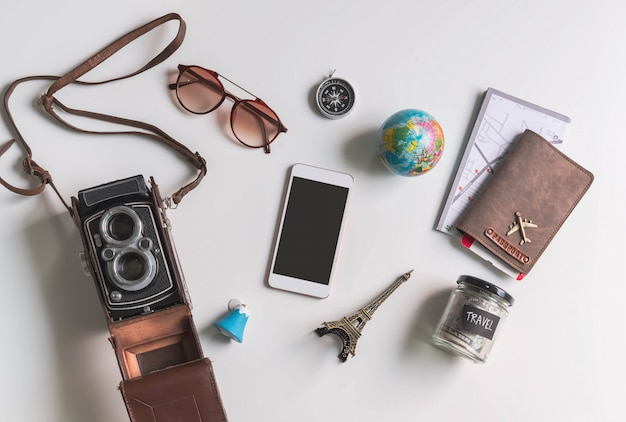 Teléfono inteligente con pantalla vacía con accesorios de viaje y artículos sobre fondo blanco con espacio de copia