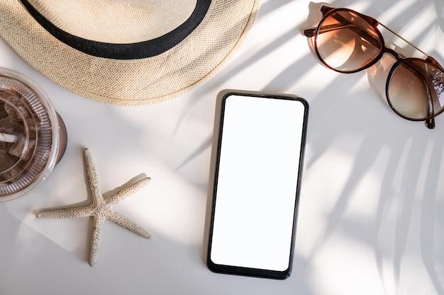 Teléfono inteligente de pantalla vacía con accesorios de viaje sobre la mesa, concepto de vacaciones de verano