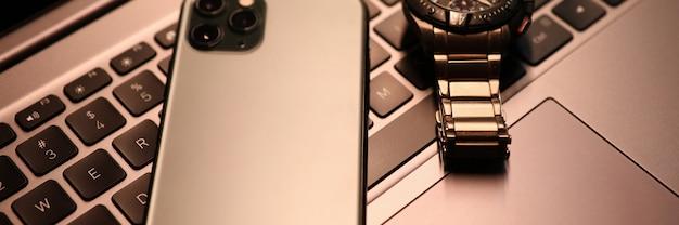 El teléfono inteligente plateado y el reloj se encuentran en el teclado del ordenador portátil en primer plano de la oficina