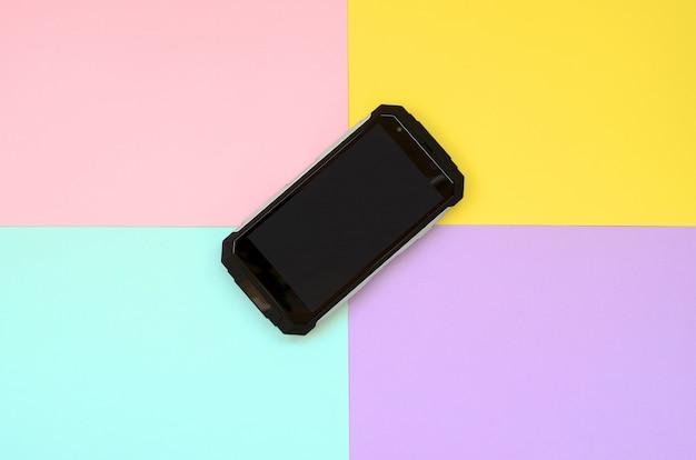 Un teléfono inteligente a prueba de golpes negro se encuentra en un fondo de color pastel
