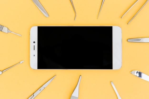 Teléfono inteligente rodeado de equipos médicos quirúrgicos sobre fondo amarillo
