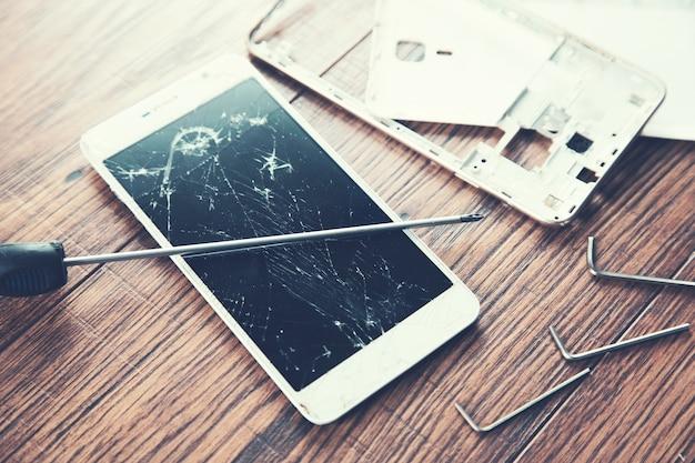 Teléfono inteligente roto con herramientas en la mesa de madera