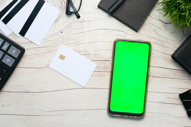 Teléfono inteligente y tarjeta de crédito en la mesa de madera, endecha plana, vista superior