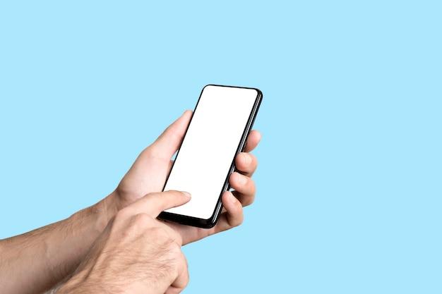 Teléfono inteligente vacío en la mano en el teléfono de la maqueta del fondo de la bandera azul coloreada con la pantalla en blanco en mínimo ...