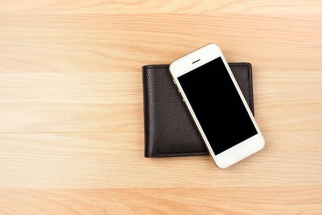 Teléfono inteligente y billetera negra sobre fondo de piso de madera. vista superior