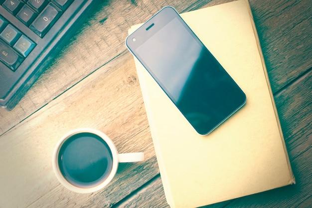 Teléfono en el libro y café en la mesa de madera