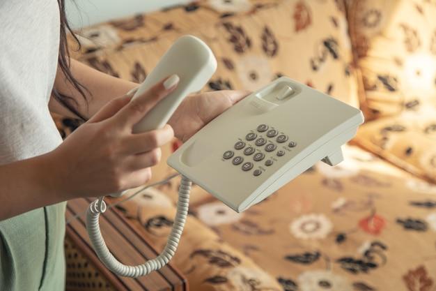 Teléfono de llamada de mano de mujer en la habitación del hotel