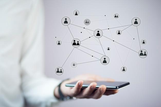 Teléfono de la mano del empresario con botones virtuales de redes sociales