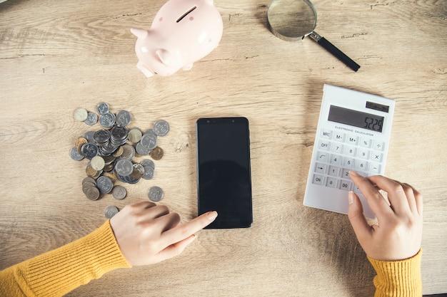 Teléfono de mano de mujer con monedas y calculadora en la mesa