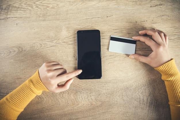 Teléfono de mano de mujer y tarjeta de crédito sobre la mesa