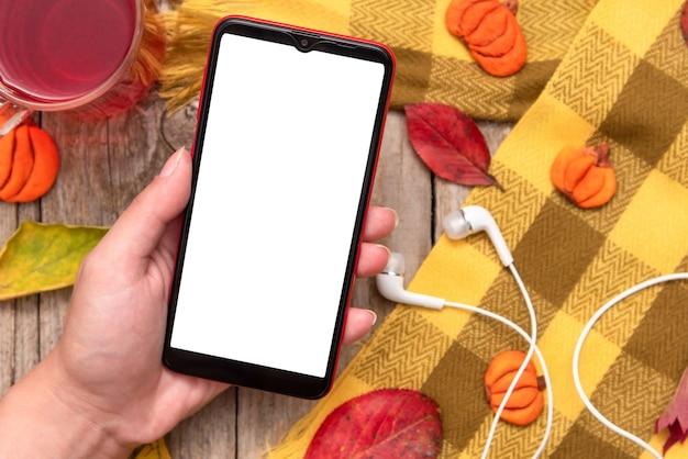 Teléfono en la mano de una niña con el telón de fondo de otoño hojas caídas y una bufanda.