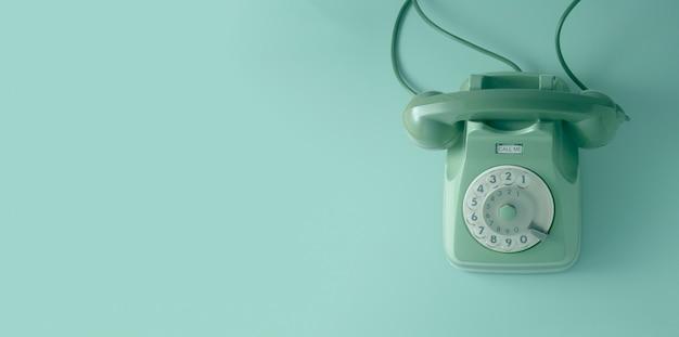 Un teléfono de marca vintage verde con pared verde.