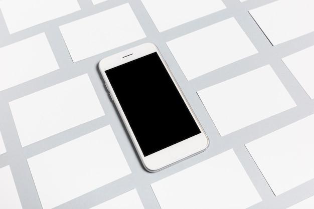 Teléfono moderno y tarjetas en blanco