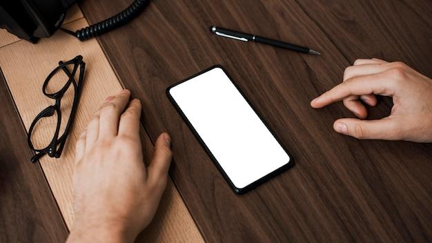 Teléfono móvil de alta vista y gafas de lectura en el escritorio