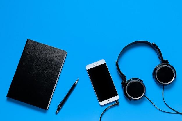 Teléfono móvil, auriculares, bloc de notas y bolígrafo.
