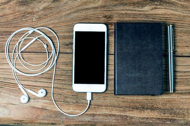 Teléfono móvil y auriculares sobre fondo de madera