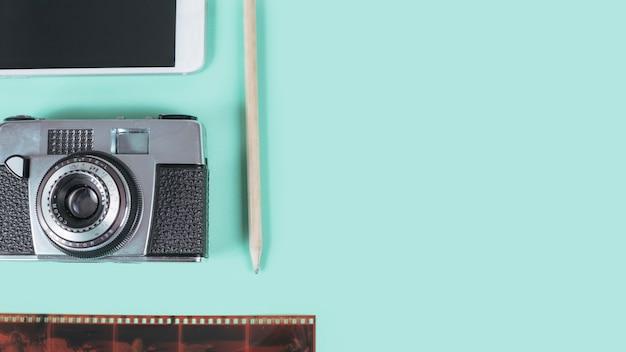 Teléfono móvil; cámara; lápiz y tira de película sobre fondo turquesa