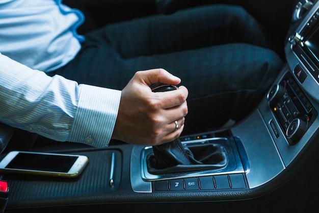 Teléfono móvil cerca de la mano del hombre que cambia la palanca de cambios mientras que conduce el coche