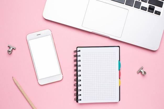 Teléfono móvil, computadora portátil y portátil en una jaula sobre un fondo rosa