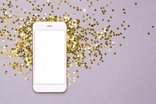 Teléfono móvil con confeti de estrellas doradas en púrpura