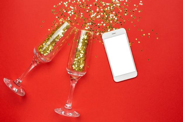 Teléfono móvil y copas de champán con confeti de estrellas doradas, concepto de navidad y año nuevo