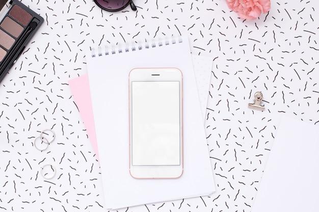 Teléfono móvil y cuaderno de mujer con cosméticos y flores.