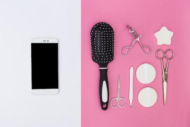 Teléfono móvil y cutícula; cepillo de pelo; tijeras; esponja; rizador de pestañas y esponja en doble telón de fondo