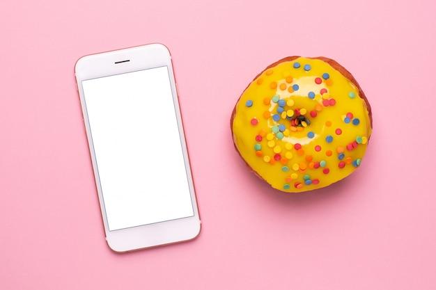 Teléfono móvil y dulce donut amarillo sobre un fondo rosa plano lay