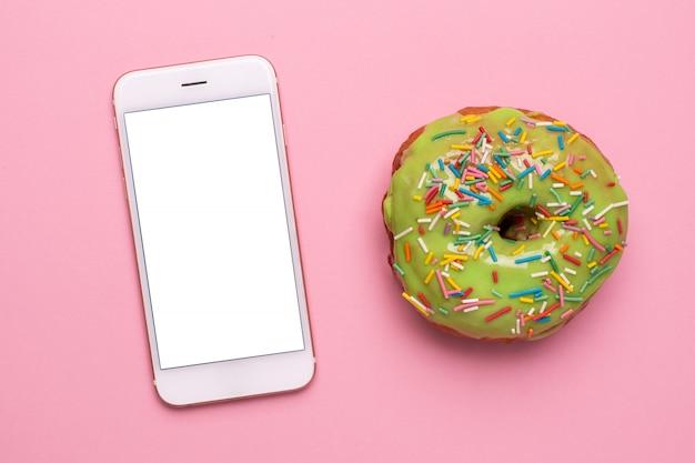 Teléfono móvil y dulce donut verde sobre un fondo rosa plano lay