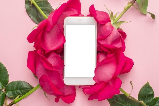 Teléfono móvil y flores rosas sobre un fondo rosa pastel